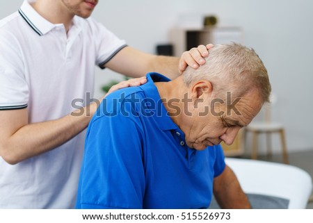 Physiotherapist examining an elderly male patient stretching and re-aligning his neck and vertebrae, close up upper body