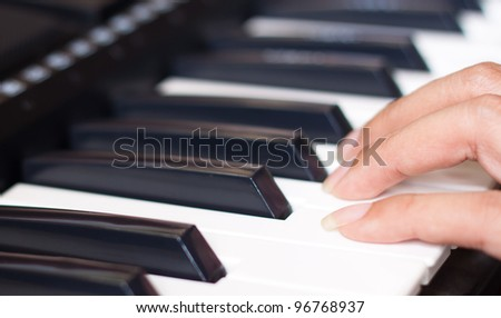 piano keyboard with woman's hand