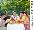 Picnic. Multi ethnic friends sharing an enjoyable meal seated at a table outdoors in the garden laughing and joking together - stock