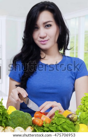 Picture of a cute Asian woman making healthy food while cutting fresh vegetables in the kitchen