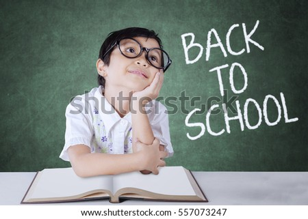 Picture of a female elementary school student daydreaming in the classroom with a book on the table