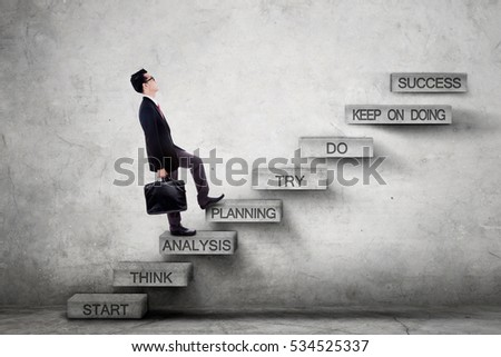 Picture of a male entrepreneur climbing a stairway while carrying a briefcase with strategy plan on the ladder leading to success