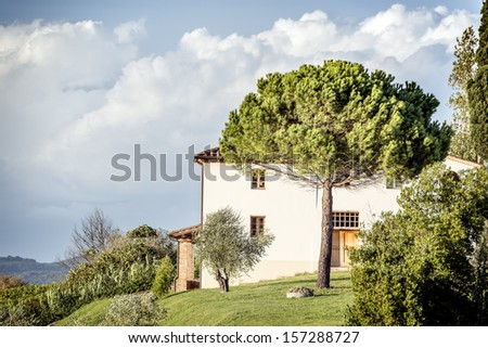 Picture of a typical house with tree and clouds on blue sky in Tuscany, Italy