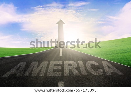 Picture of America written on the asphalt road with arrow upward at the end of a road
