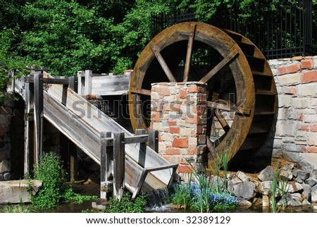 Picture of an old water wheel in a small pond.