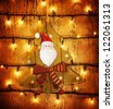 Picture of beautiful Christmastime ornament, little decorative Christmas tree hanging on wooden door adorned xmas lights, grunge glowing background, festive electrical garland, Santa Claus decor - stock photo