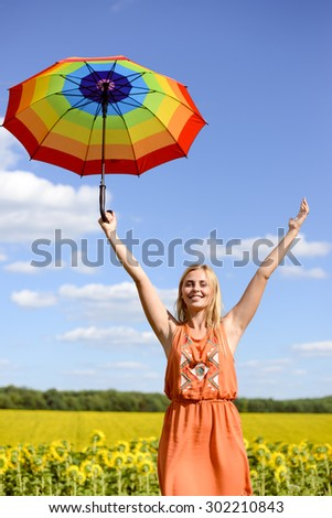 Picture of blond pretty female holding rainbow umbrella on the sunflower field outdoors background copy space