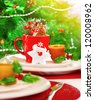 Picture of Christmas eve table setting with beautiful holiday decorations, white and red festive utensil, warm yellow candle light, Santa Claus star toy, little berry branch, New Year party - stock photo