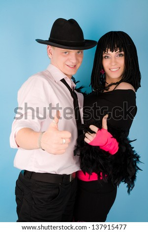 Picture of hot colorful couple showing thumbs up on blue background