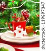 Picture of luxury festive table set, romantic candle with red tea cup and little Christmas decoration on white plate, green spruce tree decorated with beautiful toys, holiday dishware, New Year eve - stock photo