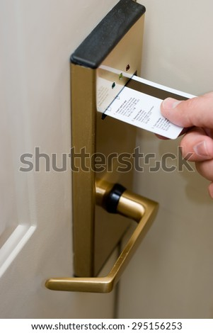 Picture of person's hand inserting a key card into a hotel room electronic door security lock to unlock the door.
