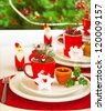 Picture of table setting for winter holidays time, holiday banquet, Christmas celebration, luxury white porcelain dishware on red festive tablecloth, New Year party, decorated evergreen tree - stock photo