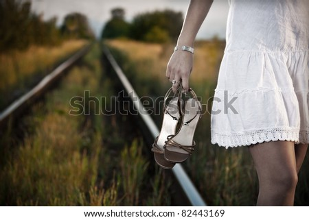 picture of young woman hand with shoes on the railway