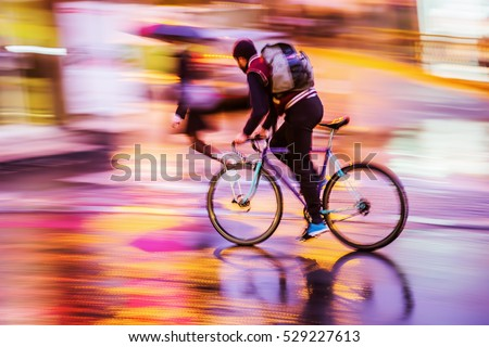 picture with camera made motion blur effect of a bicycle rider at night traffic