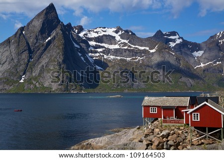 Picturesque red fishing hut on the coast of fjord on Lofoten islands in Norway
