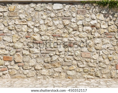 Picturesque stone and brick wall in a bright sunny day as background