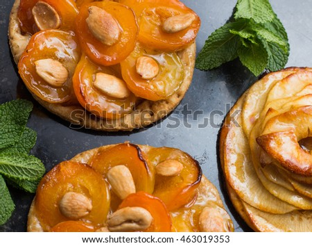 Pie with apricot and apple. Traditional french tart with fruits on dark marble background. Decorated almonds and mint leafs. Delicious dessert with copy space closeup.