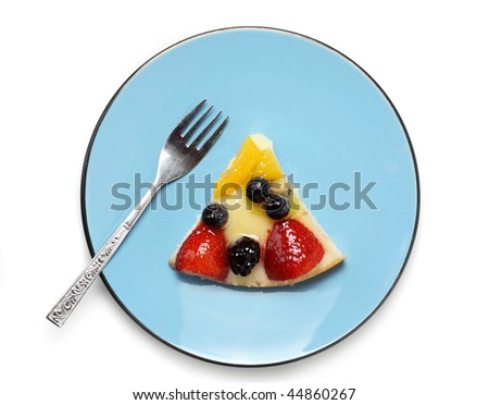 piece of fresh fruit cake in blue plate, isolated on white