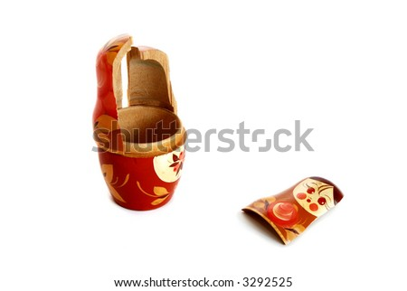 Pieces of broken nesting doll lying on a white background