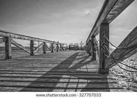 pier calm sea with long wooden walkway and boardwalk fence