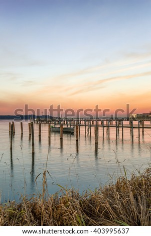 Pier with a boat on lake Chiemsee in Bavaria, Germany