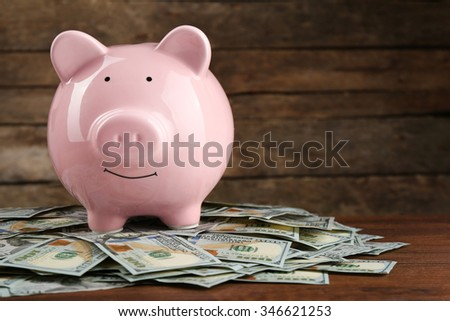 Pig money box and dollar banknotes on wooden wall background