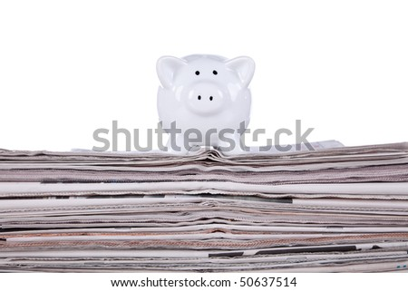Piggy bank over a stack of newspaper (selective focus)