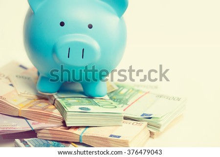 Piggy bank with stack of euro banknotes bills isolated on white background. Financial success idea concept