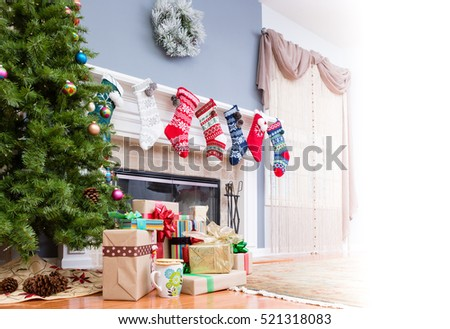 Pile of Christmas gifts under the tree with colorful stockings hanging on the mantelpiece and a high key bright copy space to the side for your holiday message
