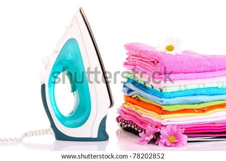 Pile of colorful clothes and electric iron  over white background