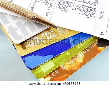 Pile of credit cards with pen and receipt