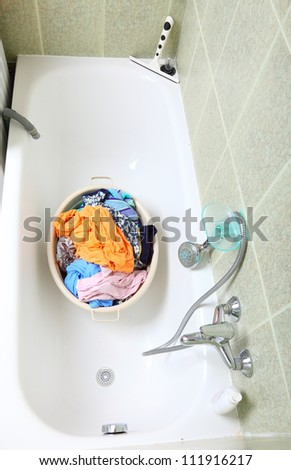 Pile of dirty laundry in bath washing machine green bathroom