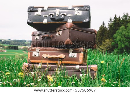 Pile of old vintage suitcases in a rural landscape