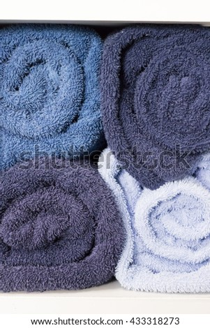 pile of rolling blue towel on white shelf