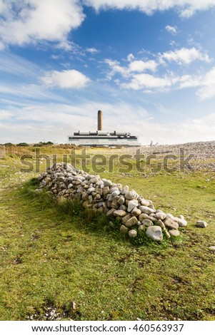 Pile of stones with Aberthaw B Coal Fired Power Station, South Wales, UK.