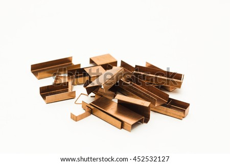 Piles of copper office staples isolated on white background