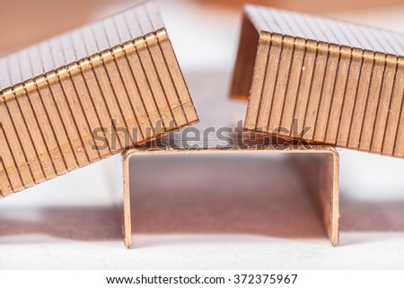 Piles of paper staples made of copper, on white
