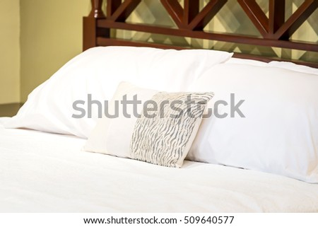 Pillows setting on white color scheme bedding.