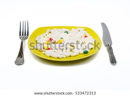 pills as dinner on a plate on white background