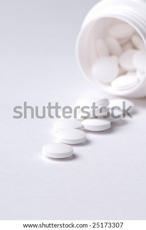 Pills spilling out of pill bottle on the white background