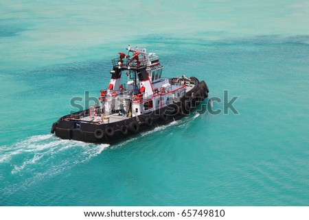 Pilot on little fire pusher tug drift through the sea at day