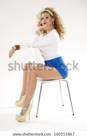 Pin-Up, beautiful girl in a classic pin up pose with blue short and blouse on a white background. American style