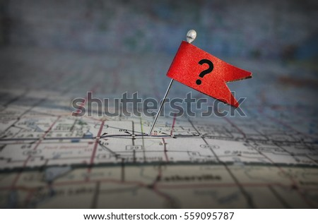 Pin with red question mark flag stuck in a map