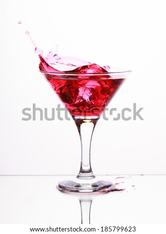 Pink alcohol cocktail in martini glass with splash on light background, selective focus