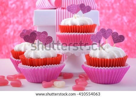 Pink and white cupcakes with heart shape toppers on white wood table with pink background for Mothers Day, Valentine or feminine birthday celebration.