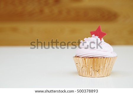 pink cupcake with cream on white table