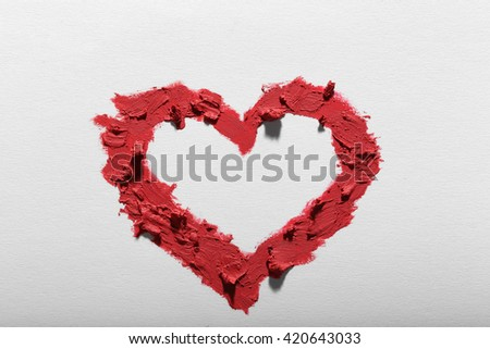 Pink lipstick smeared in heart shape isolated on white background, close up