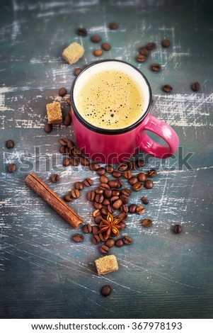Pink mug with hot coffee and spices on Shabby background