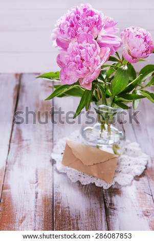 Pink peonies in a glass jug and a letter in an old envelope