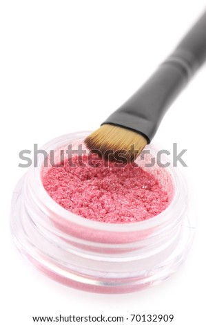 Pink powder eyeshadow in jar with brush close-up on white background.